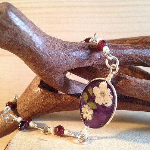 Bracciale fiori veri e pietre granato, fondo viola