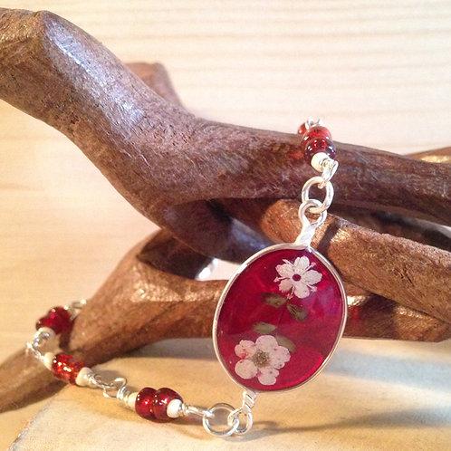 Bracciale fiori veri e pietre fondo rosso