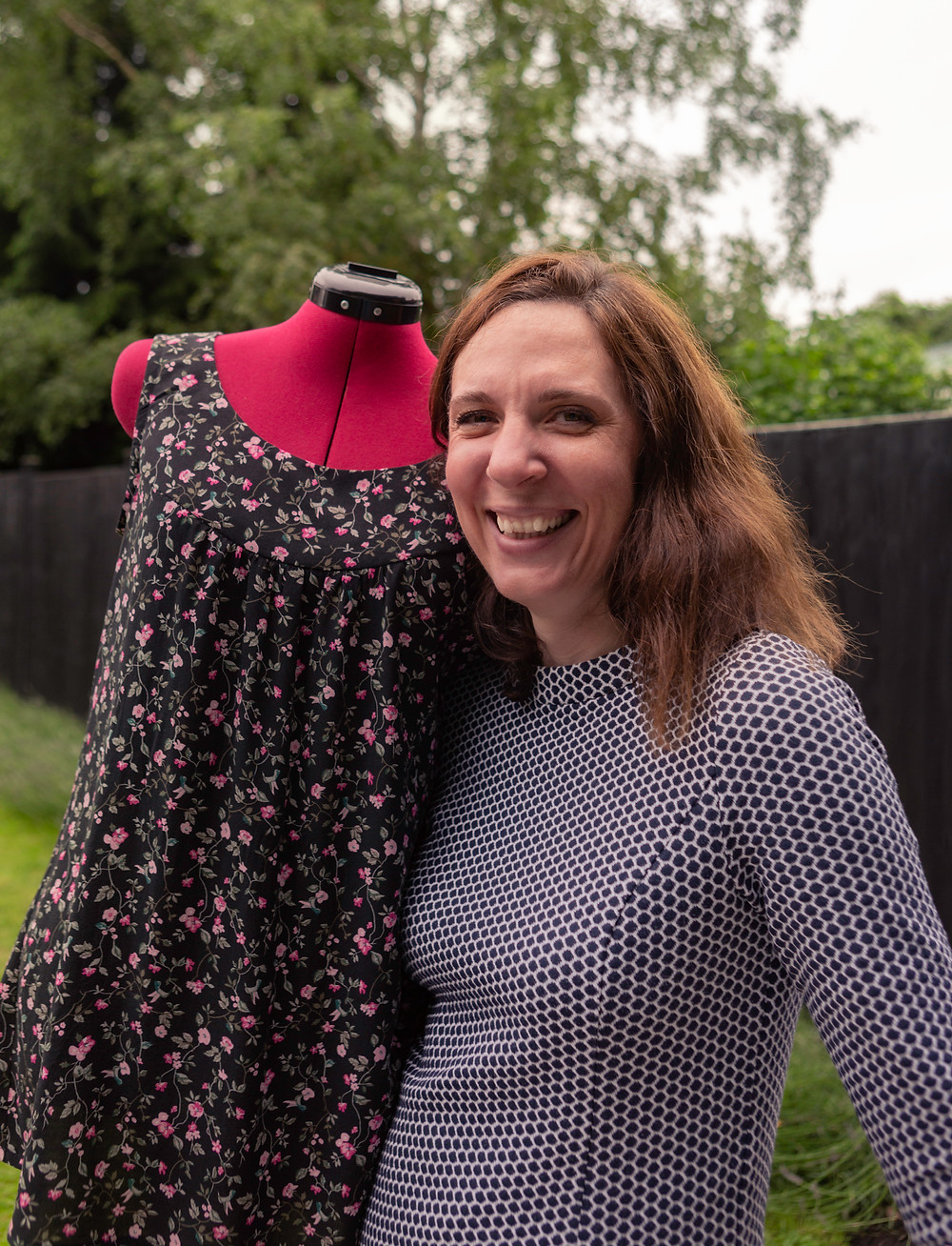 A smiling Jo Watson, of Watson Designs, standing in a garden holding a bodice wearing a top she has sewn