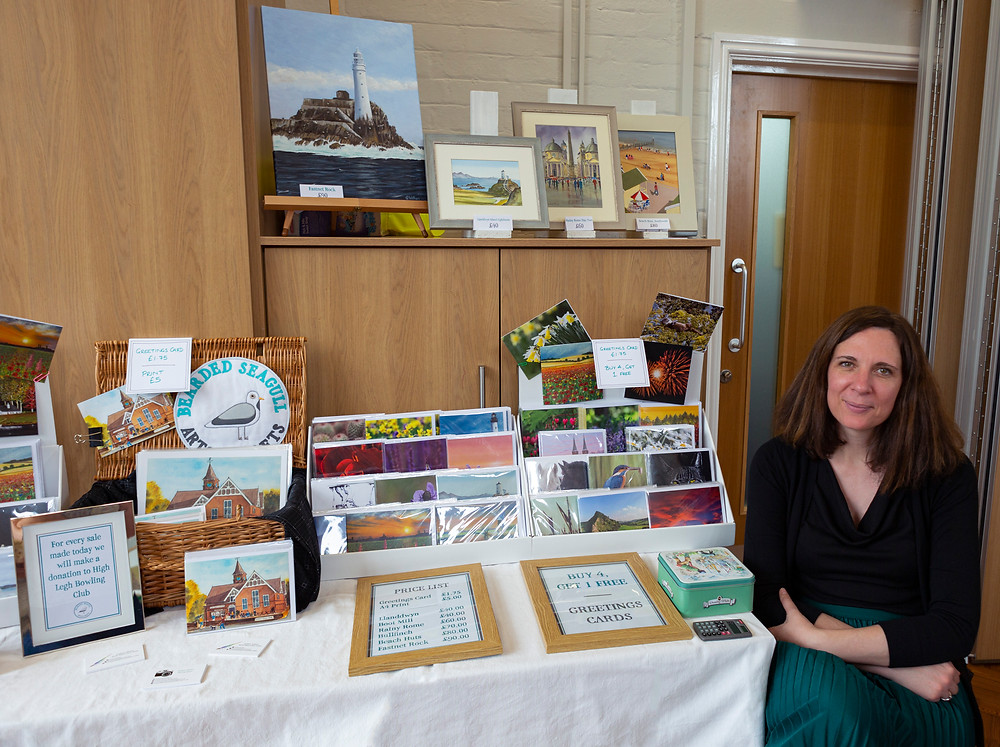 Jo Watson, Bearded Seagull Co-Founder, sitting next to a craft stall displaying paintings, greetings cards, prints and signs