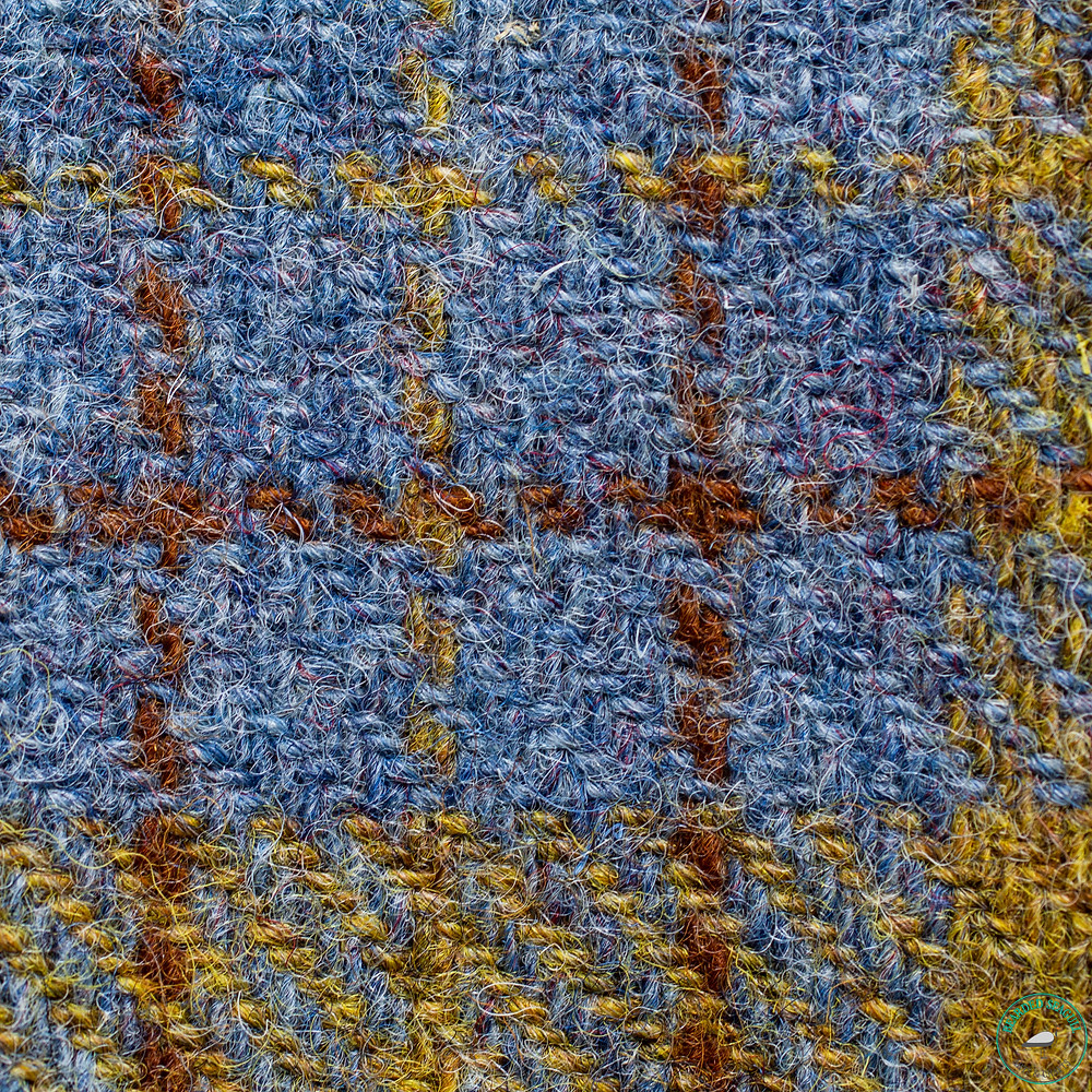Plaid pattern weaved into a piece of blue Harris Tweed