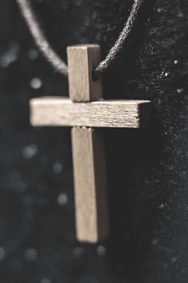 cross necklace on string with black background