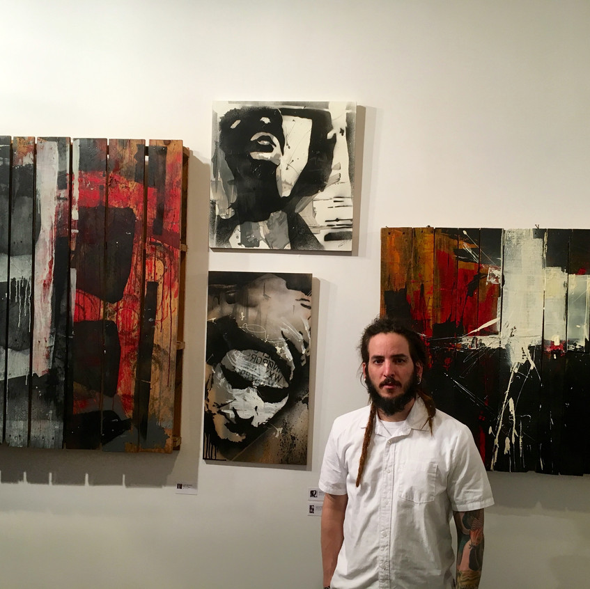Artist Frank Henriquez with his work