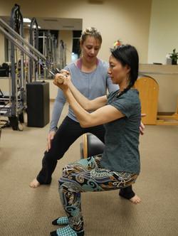 physical therapist, patient, squat, pilates, tower, pilates, pilates rehab, verbal cue