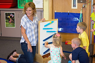 Teacher and 3 students working on a magnetic board with balls that roll from different tunnels in a preschool