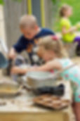 A young boy and a little girl cooking in a nature garden kitchen
