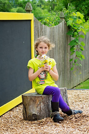 Young girl sitting on a tree trunk holding daisies in the nature playground.