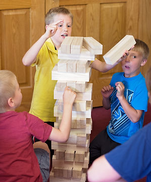 3 students building with life size jenga pieces.  One boy looks scared as if the jenga blocks are going to fall on him.
