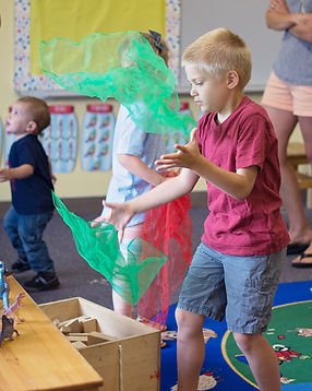 Preschool classroom with a boy throwing scarves in the air.