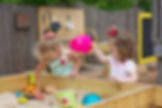 2 preschool girls playing in a sand table outside.