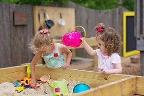 Two preschool children playing in a sandbox.