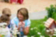 Teacher looking at 2 preschool students in a nature garden with daisies