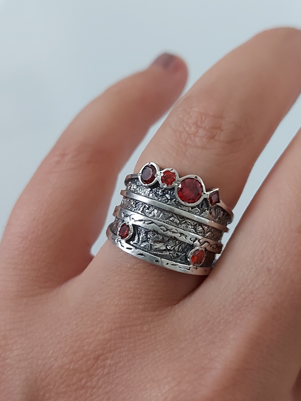 silver ring with zirconia gemstones on a finger