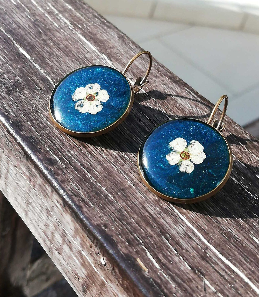 Handmade blue earrings with a white flower