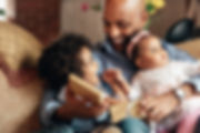 young-boy-smiles-at-father-holding-baby-