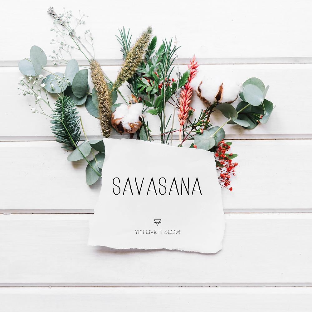 Trozo de papel que lee savasana de Yiyí Live it slow yoga con hojas de eucalipto y fondo de madera blanco