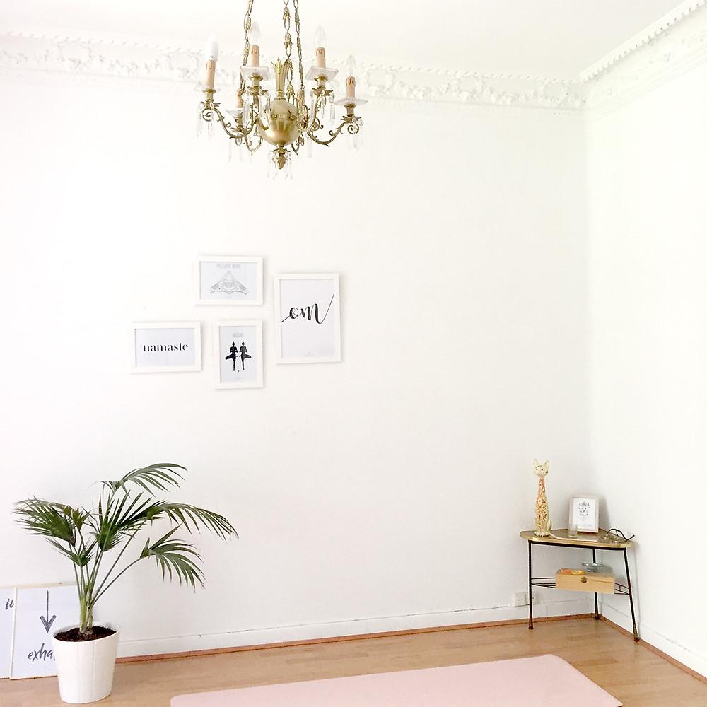 Shala de yoga con una lámpara de araña cuadros con láminas de yoga y om y una planta