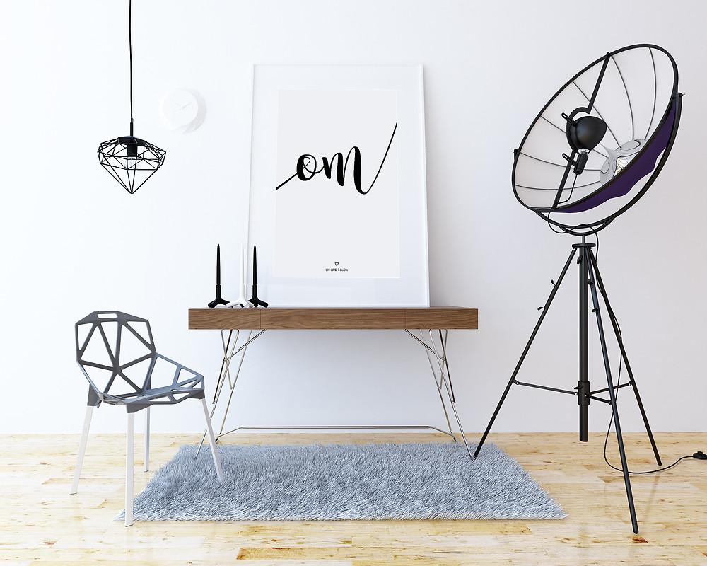 Imagen de una lamina colgada en un cuadro que pone live it slow de la diseñadora yiyi live it slow yoga, una planta, un reloj de arena, un libro y una silla