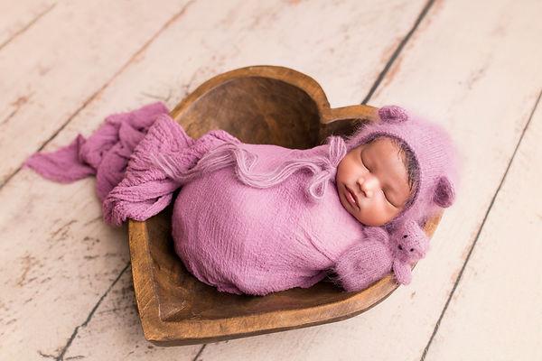 Beautiful newborn baby girl in heart shaped bowl, with pink newborn wrap, bear, bonnet. Newborn sleeping baby, JaemieHillbsi Photography.