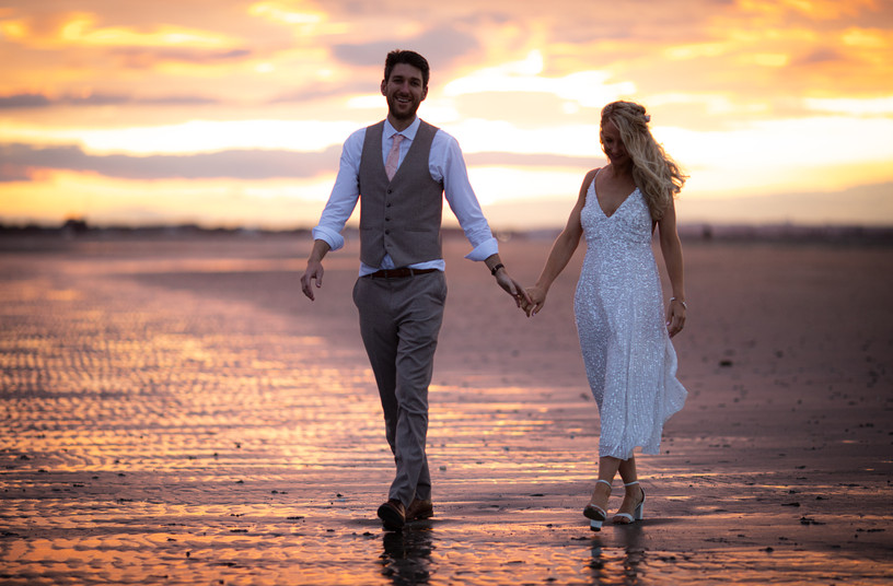 Wedding photographer with bride and groom on a sunset beach walk West Sussex Chichester