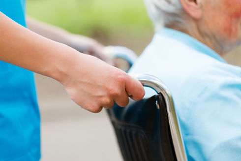 Elderly woman in wheelchair pushed by nu