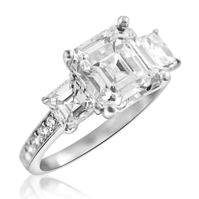 Asscher Cut Triple Diamond Engagement Ring   3.10 carat asscher cut Diamond surrounded by two Diamonds totaling in 1.08 carats, with another .31 carats of Diamonds around the band, set in Platinum.  ​