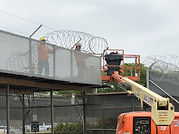 Construction crane working on chain link fence with barbed wire