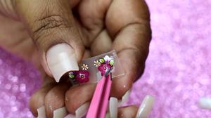 Manicure retirando adesivo de unha da cartela com uma pinça