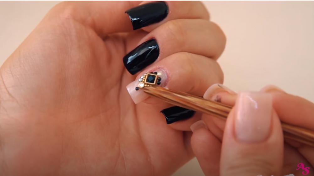 Manicure aplicando pedraria na unha