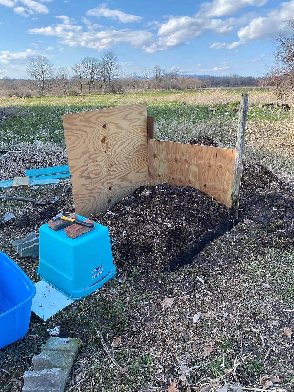 A compost pile bin made from plywood under construction, with two of four walls up.