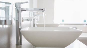 water-pouring-from-faucet-in-modern-bath