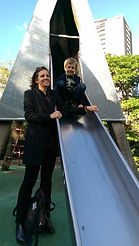 Monica standing by her son Nils on slide