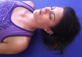 Woman resting on yoga mat in YogAcu Workshop