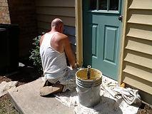 Painter painting a door.