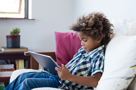 Little african boy sitting on sofa and playing game on digital tablet. Portrait of a young