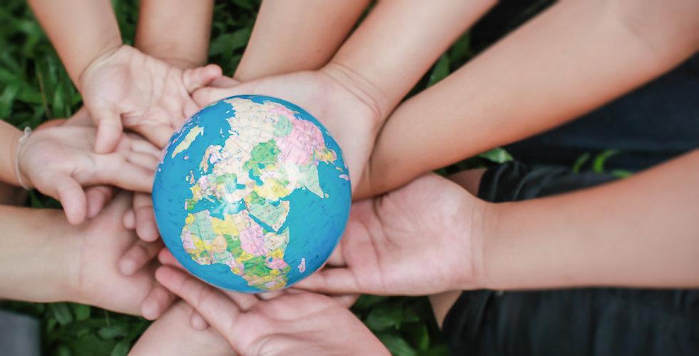 Closeup children hands holding earth ( blur ) over green grass background. World harmony g