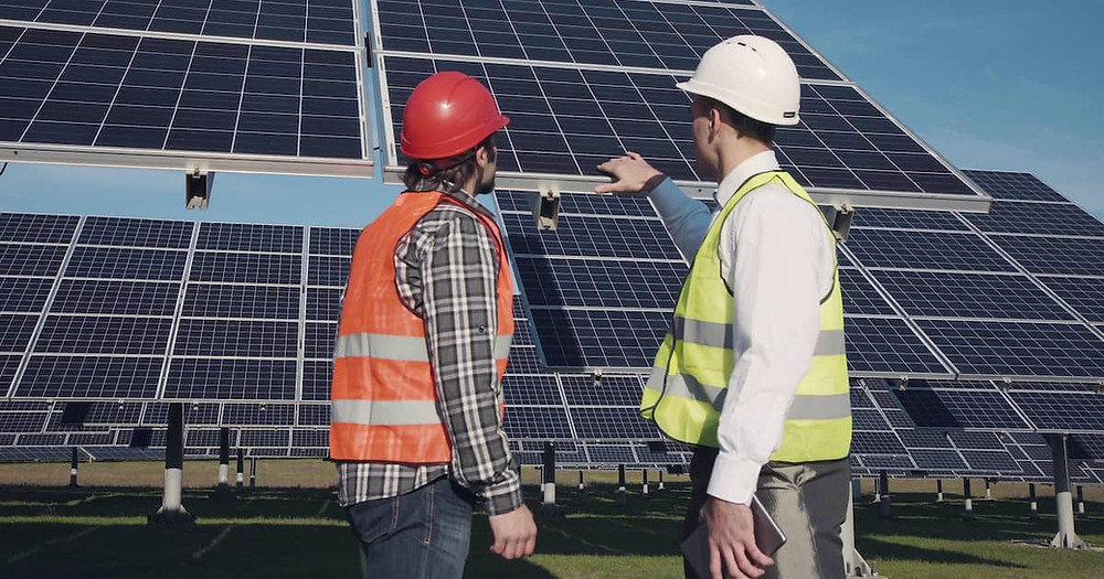 Two men in hard hats and safety gear, one explaining solar panels