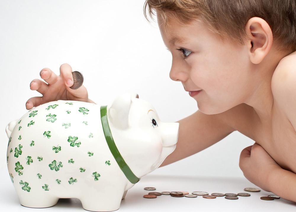 kid saving with piggy bank
