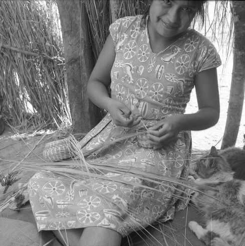 Mujer wichi tejiendo una cesta