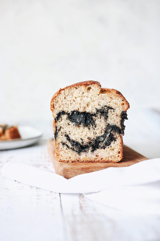 Štruca bezglutenskog kruha od banane sa punjenjem od crnog sezama na drvenoj dasci na bijeloj podlozi.