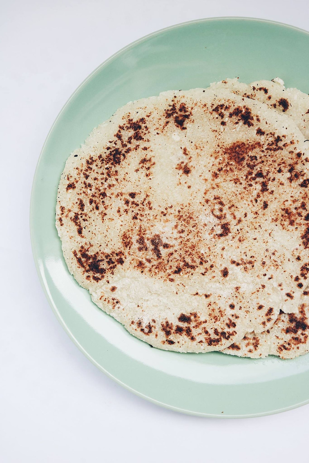 Cauliflower tortillas on a blue plate.