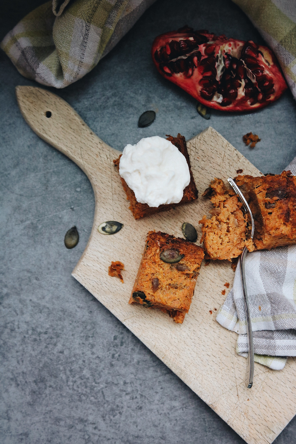 Carrot cake bars lay on a wooden cutting board, cream cheese frosting on top of one cake piece, pomegranate seeds in the background, pumpkin seeds scattered around the scene.