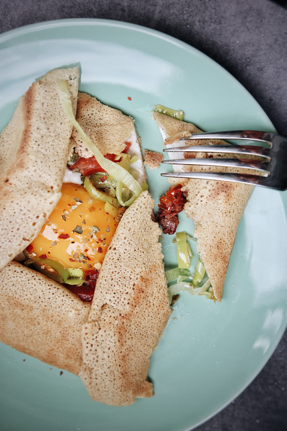 A buckwheat crepe is on a blue plate, a fork has cut a piece of the crepe. Filled with egg, leeks, and tomatoes.