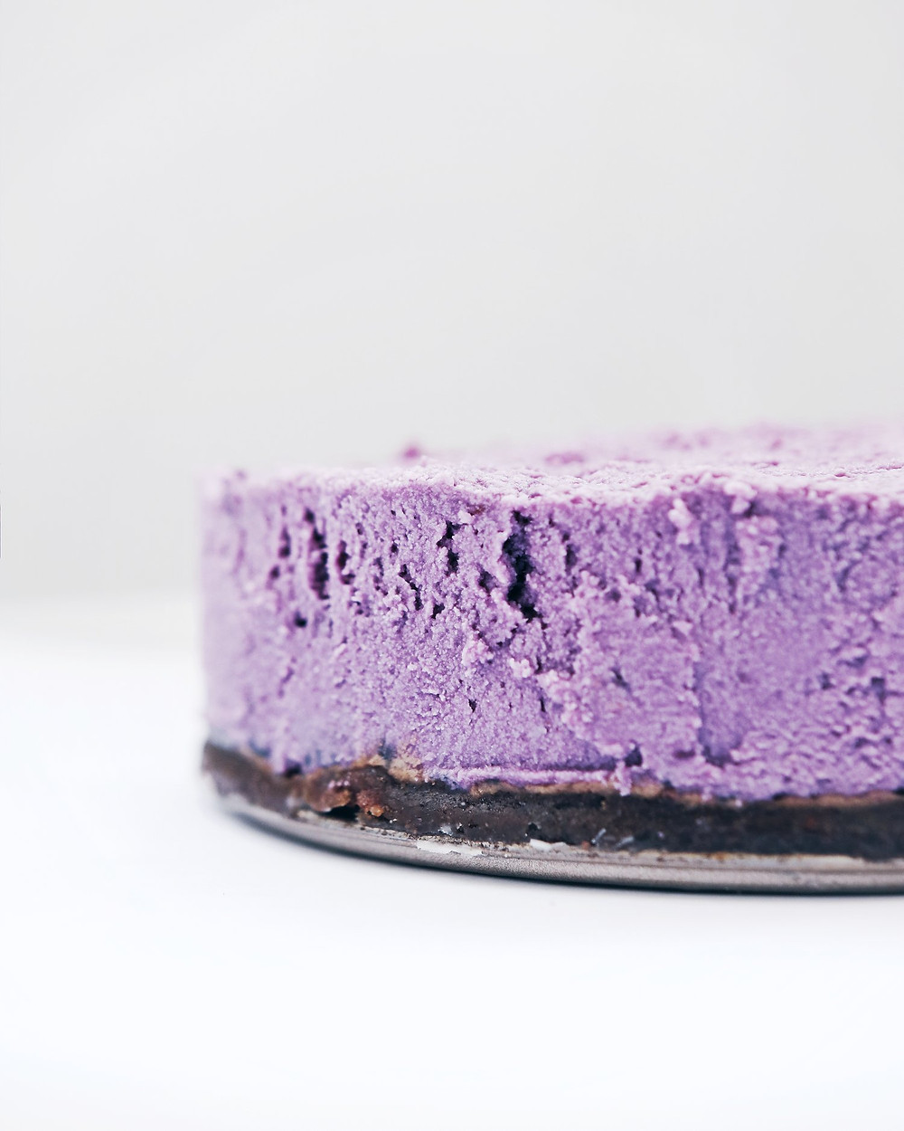 A purple sweet potato cheesecake is viewed from the side. A dark base made from dates and sunflowers is visible along with the violet filling.