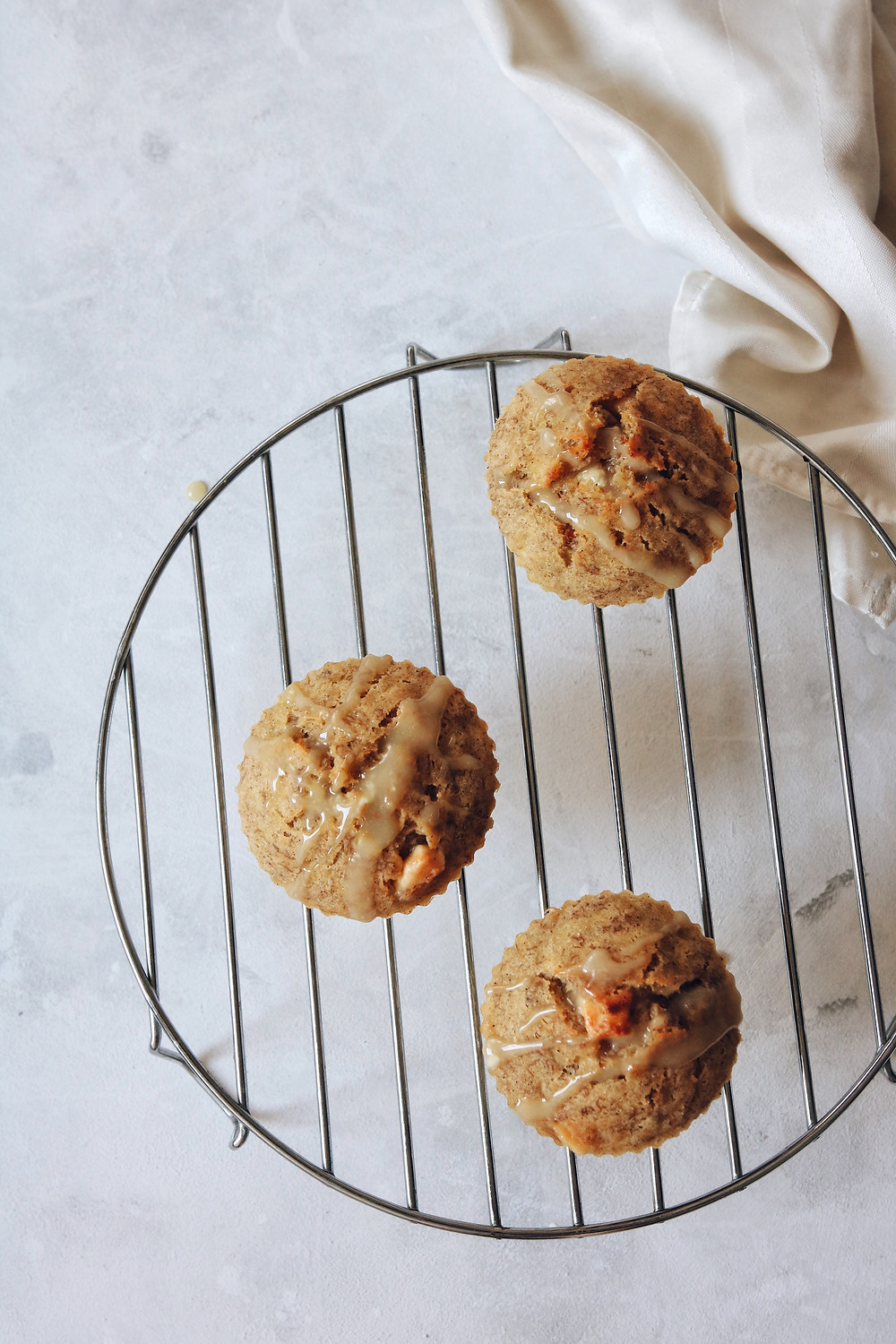 Three banana white chocolate and cinnamon muffins cool down on a cooling rack, a birds eye view.