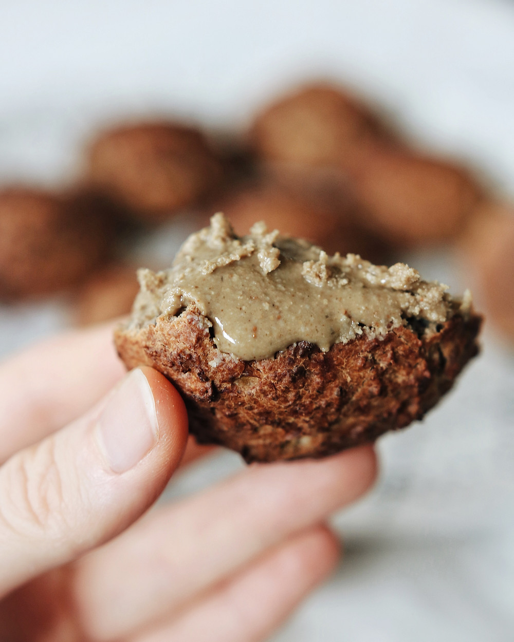 A closeup view of a banana bread cookie slathered with sunflower seed butter.