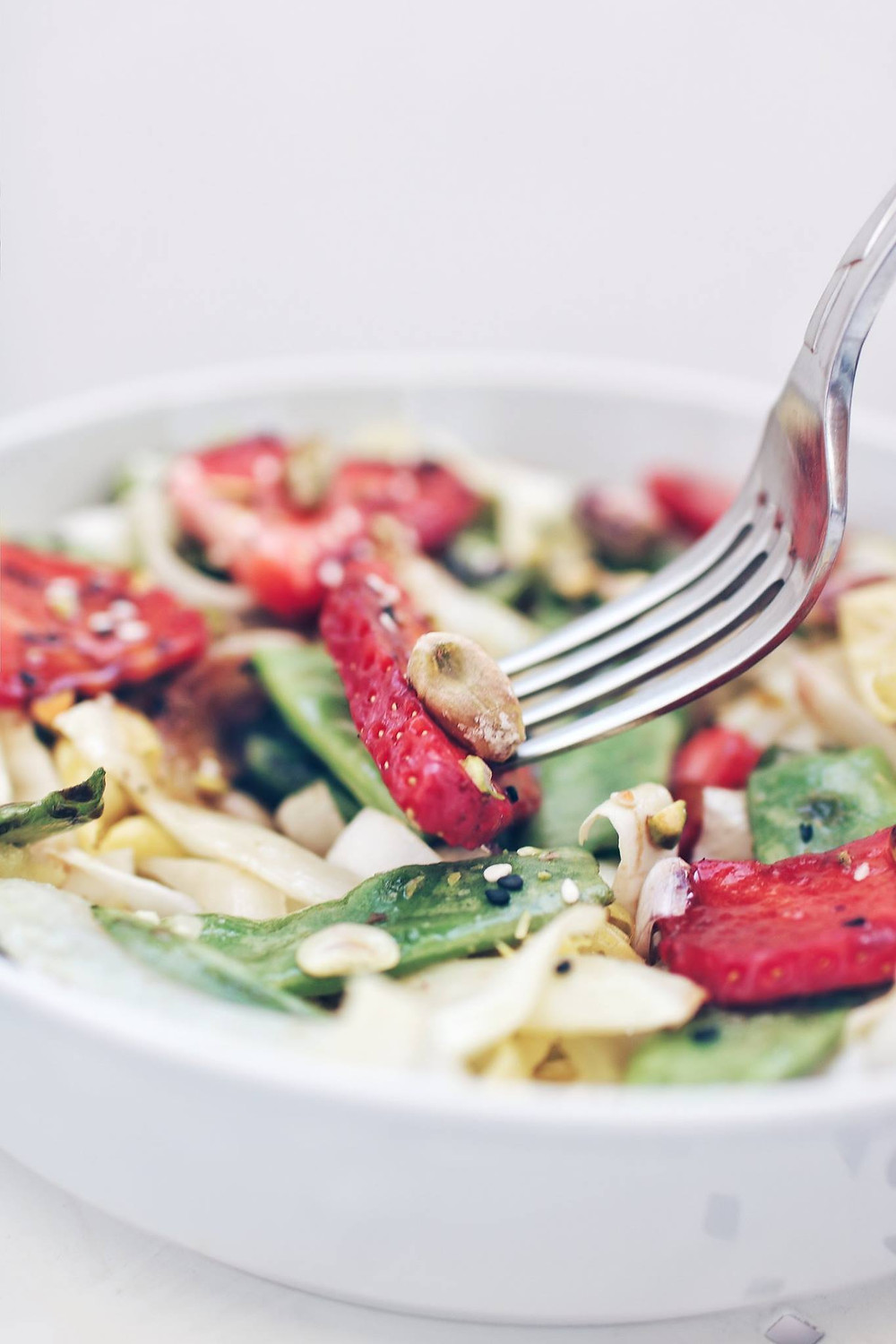 A fork grabs a piece of strawberry and pistachio from a spring salad.