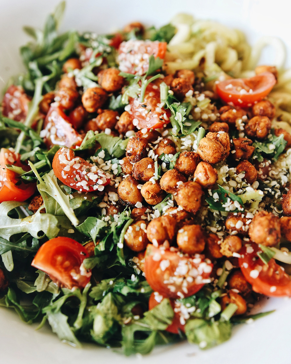 A closeup of a zucchini noodle salad featuring crispy spicy chickpeas and hemp seeds.