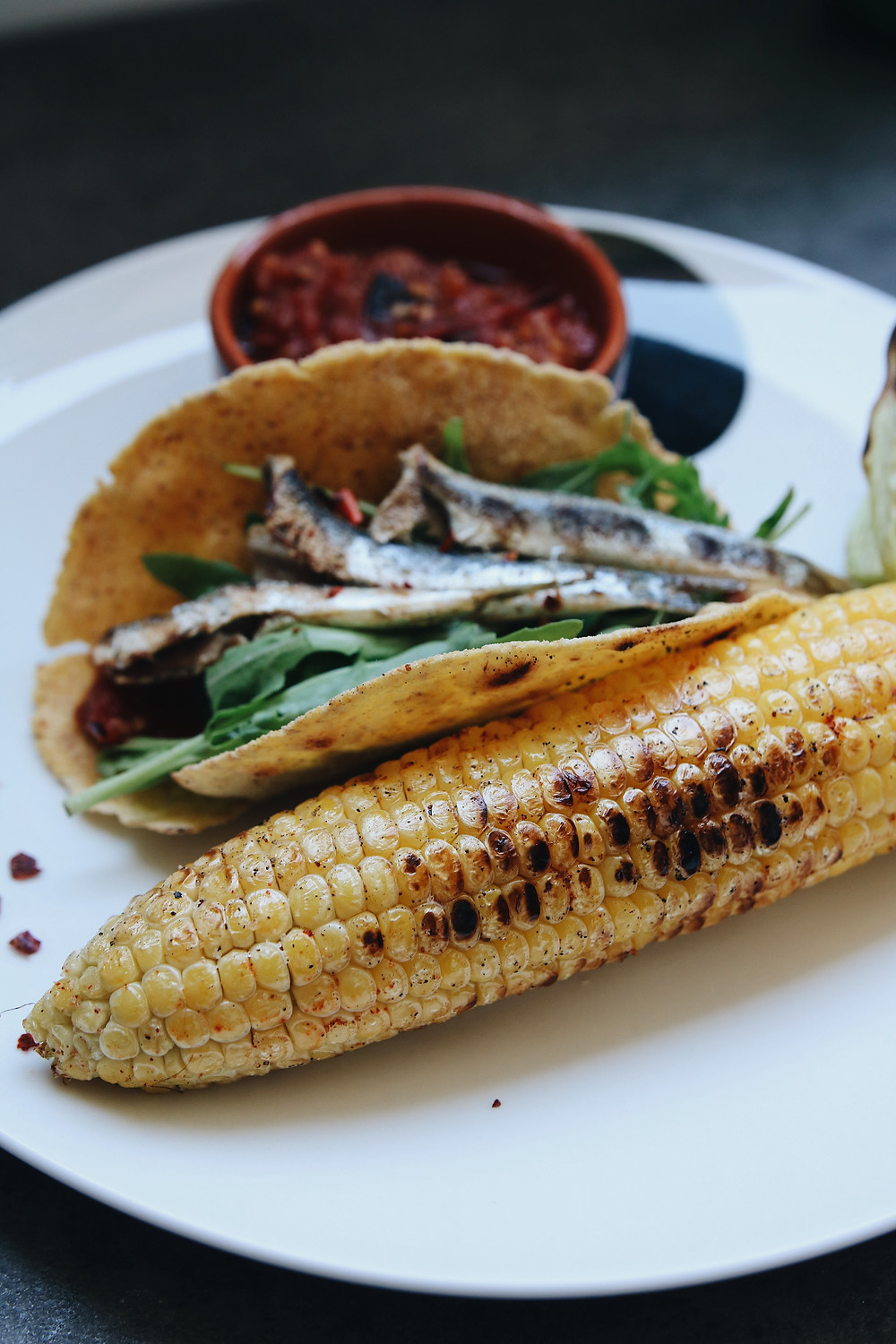 A grilled corn cob on a plate, fish taco and salsa in the background.