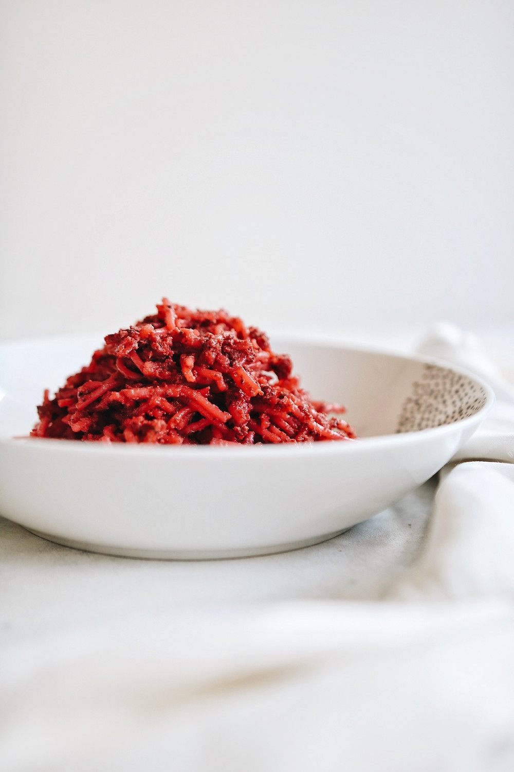 Gluten free pasta with a red pesto made of beets and toasted pumpkin seeds in a white bowl on a white background.